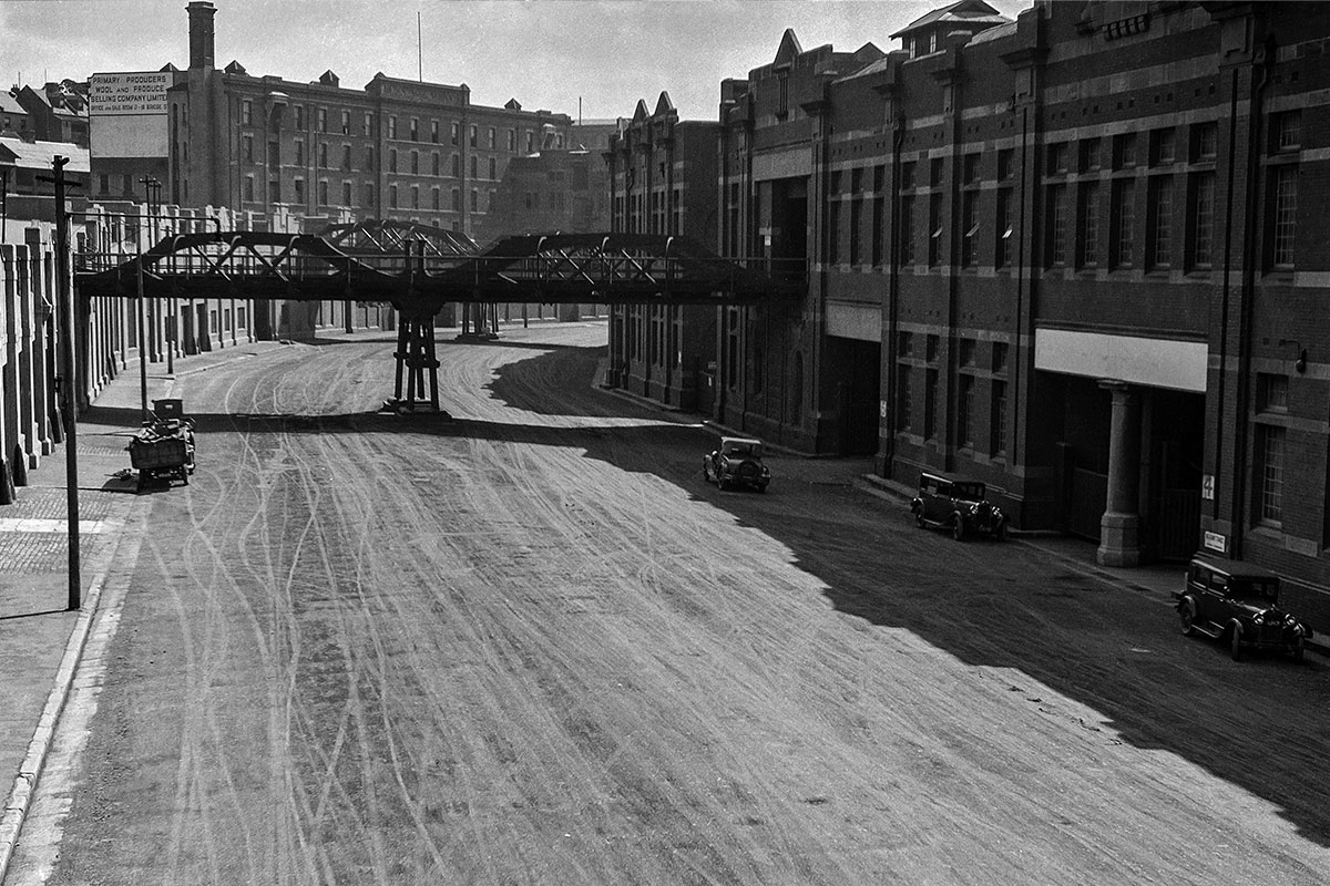 View SW showing completed roadworks in Hickson Rd, vehicles and overhead bridges linking wharves and stores on southern side. 1930's