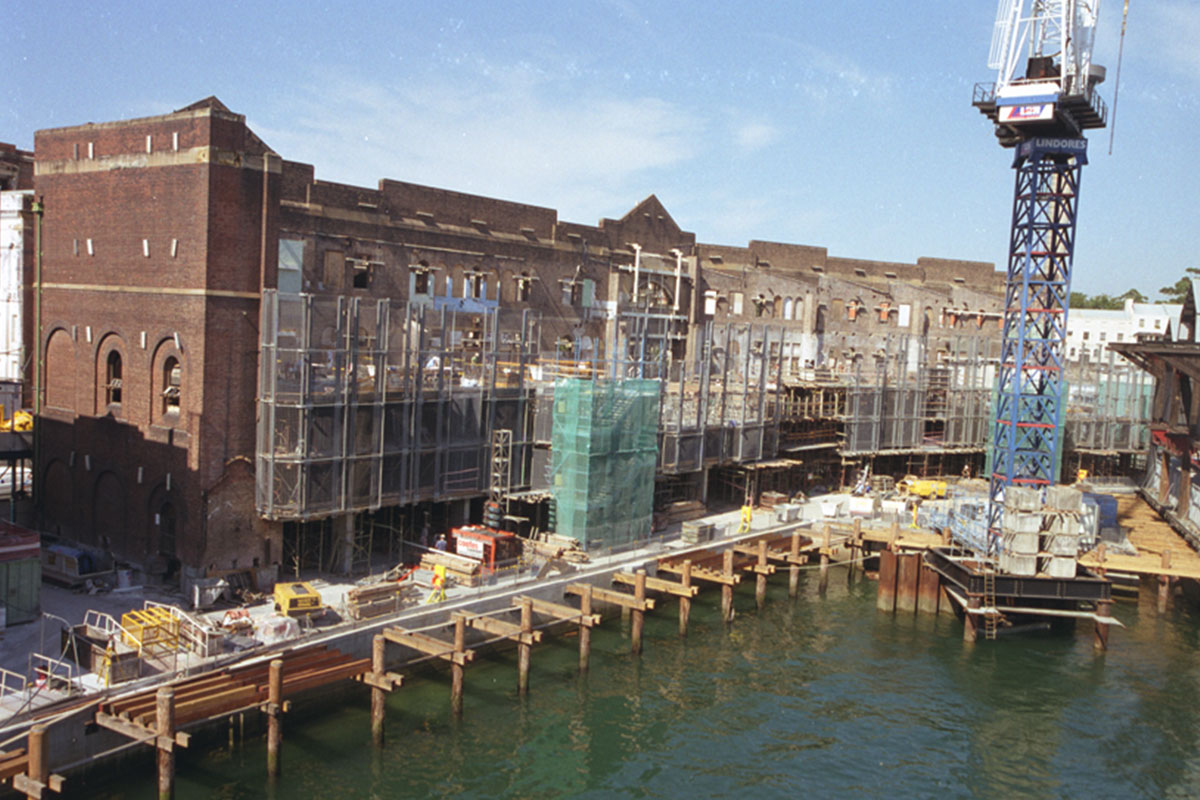 View of the Walsh Bay Finger Wharf renovation showing scaffolding, workmen, construction equipment, site crane & boardwalk pylons. 2002
